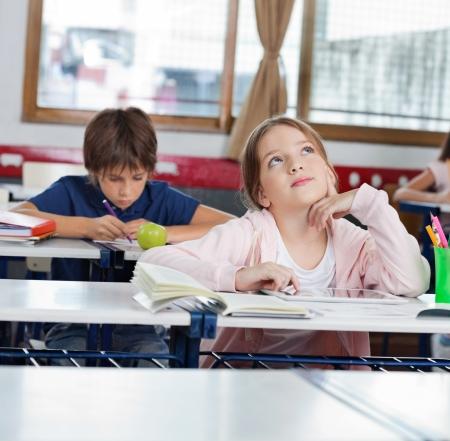 bambini pensierosi: Riflessivo scolaretta guardando mentre con tavoletta digitale con i compagni di classe in fondo all'aula Archivio Fotografico