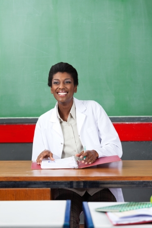 Happy young African American teacher looking away while sitting with binder at desk in classroom photo