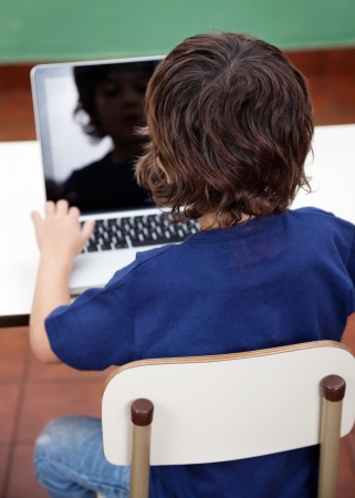 computer class: Rear view of boy using laptop at desk in kindergarten Stock Photo