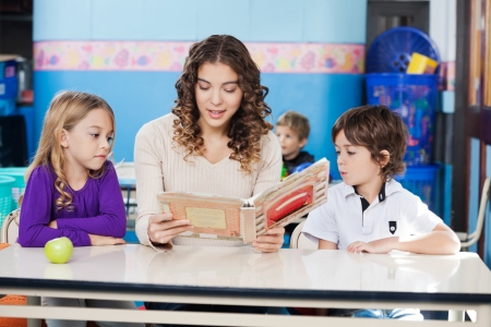 Beautiful teacher reading book while children listening to her in classroom photo