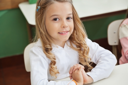Portrait of cute little girl sitting with hands clasped at desk in classroom photo