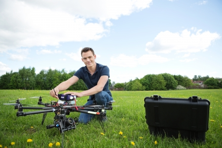 Portrait of young technician assembling octocopter drone crouching in park photo
