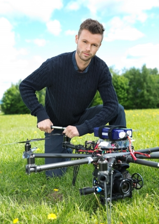 Portrait of confident young technician fixing propeller of UAV octocopter in park photo