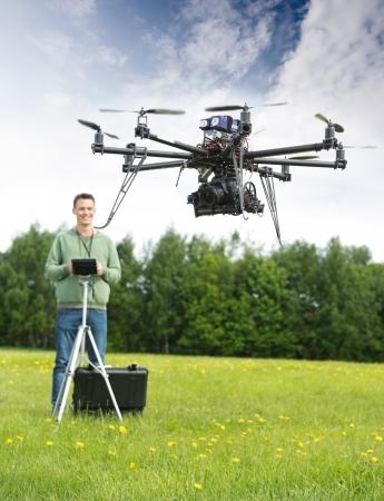 pilotos aviadores: Hombre joven con el mando a distancia de vuelo UAV helicóptero en el parque