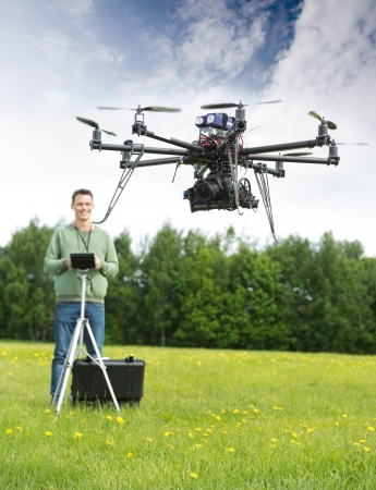 Young man with remote control flying UAV helicopter in park photo