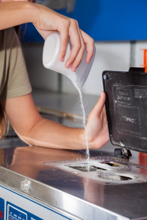 laundromat: Cropped image of woman pouring detergent powder in washing machine in laundromat