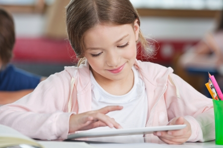 Little schoolgirl smiling while using digital tablet at desk in classroom photo