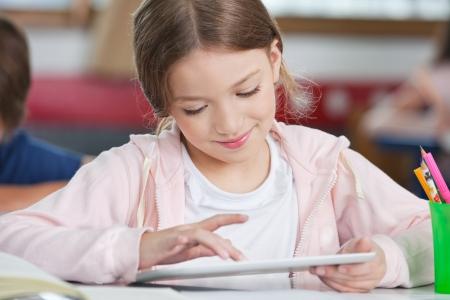 niños estudiando: Pequeña colegiala que sonríe mientras que usa la tablilla digital en el escritorio en el aula
