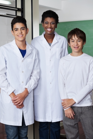 Portrait of young African American teacher with male students standing together in science lab photo