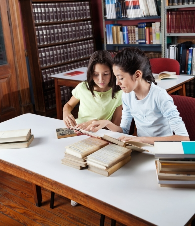 elementary students: Little schoolgirl showing book to classmate while studying at table in library