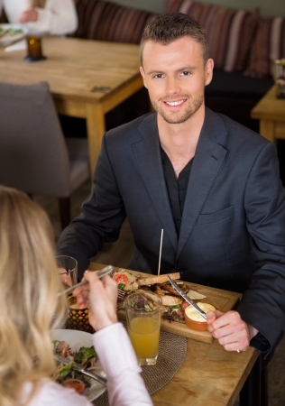 business dinner: Portrait of young businessman having food with female colleague in cafe