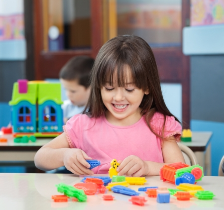 Happy little girl playing with colorful blocks at desk in classroom photo