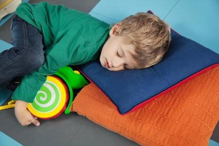 playschool: Cute boy sleeping with toy in kindergarten