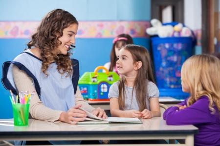 Young preschool teacher teaching little girls in classroom photo