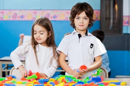 Portrait of cute preschooler boy with female friend playing blocks in classroom photo