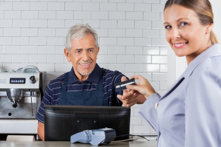 Portrait of female customer giving credit card to senior cashier in supermarket photo