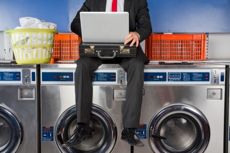 Low section of young businessman using laptop while sitting on washing machine photo