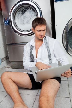 Young businessman using laptop while sitting on floor in laundry photo