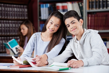 Portrait of teenage couple holding hands while sitting together at table in library photo