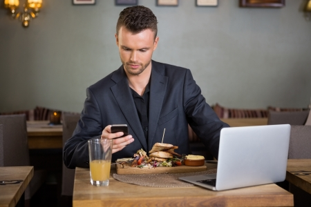 man coffee: Young businessman text messaging on cellphone while having sandwich in coffeeshop Stock Photo