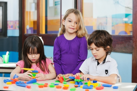 Portrait of little girl with friends playing blocks in kindergarten photo