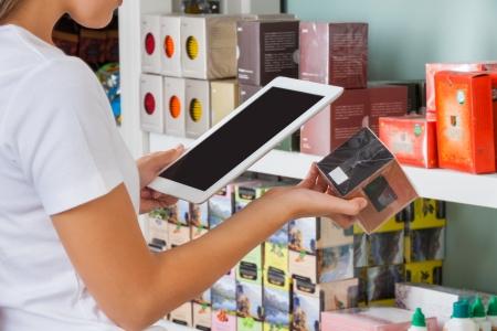 codigos de barra: Secci�n media de una mujer joven de escaneo de c�digo de barras a trav�s de la tableta digital en el supermercado