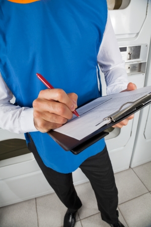 Low section of young male helper with clipboard checking list in laundry photo