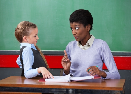 Young African American female teacher scolding schoolgirl at desk in classroom photo