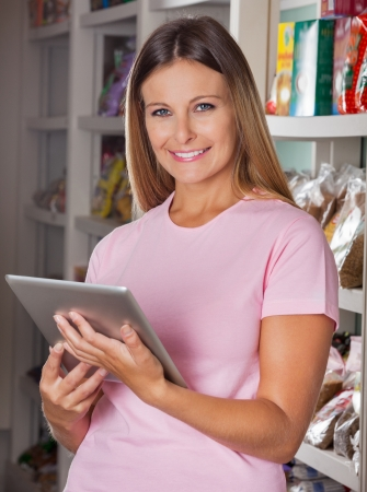 Portrait of happy mid adult woman with digital tablet in supermarket photo
