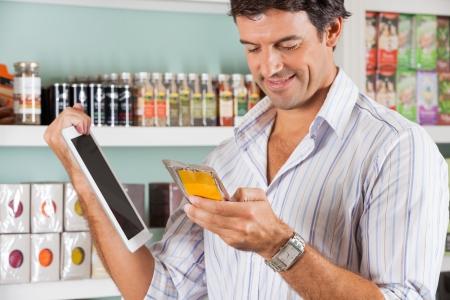 tiendas de comida: Mediados cliente var�n adulto con el producto comprobando tableta digital en la tienda de comestibles