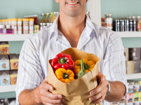 Midsection of male customer showing bellpeppers in paper bag at supermarket photo