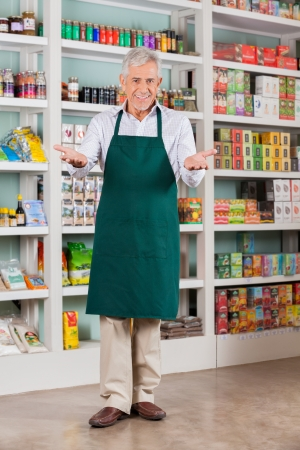 Full length portrait of senior male store owner welcoming in supermarket photo
