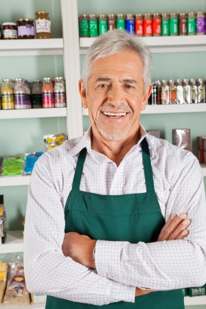 Portrait of senior male owner with hands folded smiling in grocery store photo