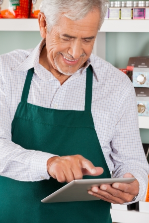 Happy senior male owner using digital tablet in grocery store photo