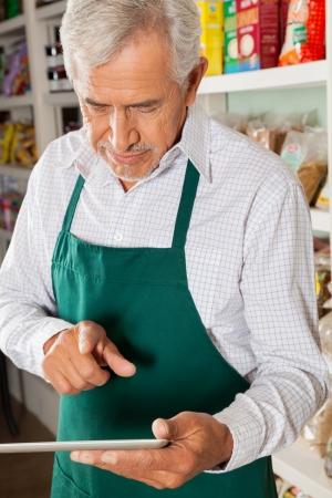 retailer: Senior male owner using digital tablet in grocery store