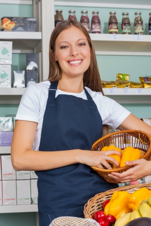 Portrait of beautiful young saleswoman holding vegetable basket in grocery store photo
