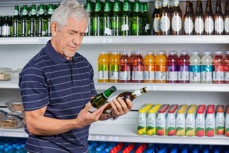 store shelf: Senior man comparing beer bottles at supermarket