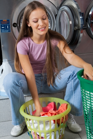 Beautiful young woman with basket of clothes at laundry photo