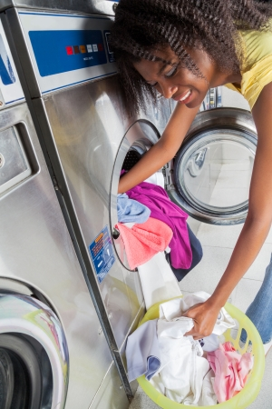 laundromat: Young African American woman loading dirty clothes in washing machine Stock Photo