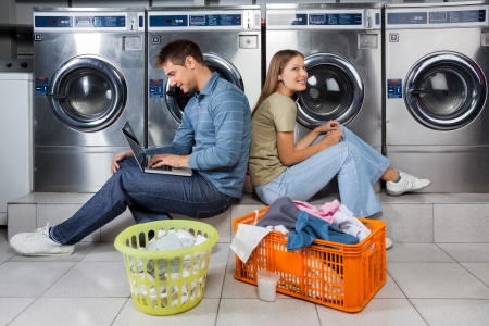 man laundry: Man using laptop and woman listening to music while sitting back to back at laundry Stock Photo