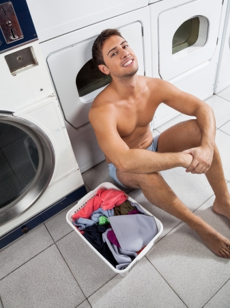 automatic machine: High angle view of young man with laundry basket waiting to wash clothes