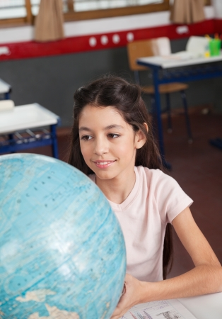 Cute little schoolgirl smiling while searching places on globe at desk in classroom Stock Photo - 22530943