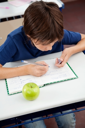 dishonest: High angle view of schoolboy copying from cheat sheet at desk during examination