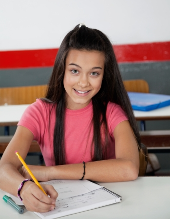 Portrait of teenage schoolgirl writing in book at desk in classroom Stock Photo - 22530962