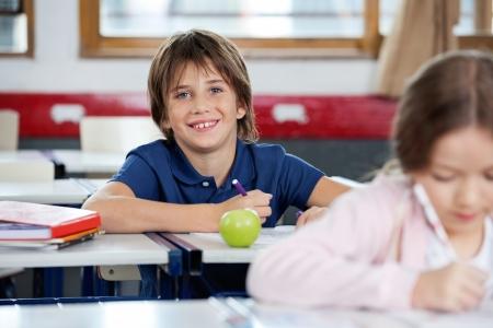 Portrét šťastný školák kreslení s vnitřním spolužákem v popředí v učebně Reklamní fotografie - 22614100