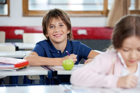 Portrait of happy schoolboy drawing with female classmate in foreground at classroom photo