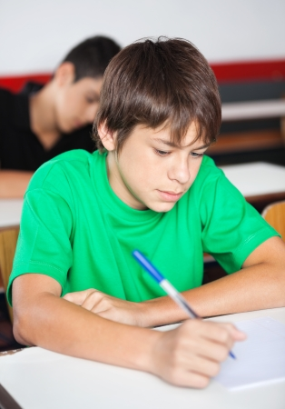 test paper: Teenage schoolboy writing at desk with classmate in background during examination Stock Photo