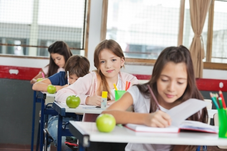 Portrait of cute schoolgirl sitting at desk with classmates in a row photo