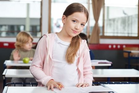 Portrait of cute little girl studying while standing at desk with classmates in background photo
