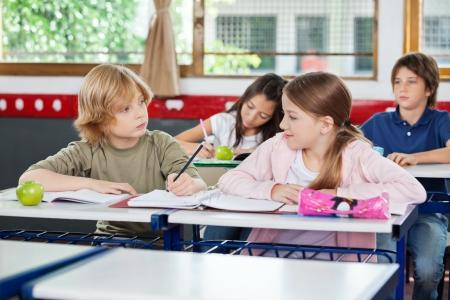 Malý školák při pohledu na školačka při psaní u stolu s spolužáci sedí v pozadí Reklamní fotografie - 22614141
